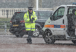© Licensed to London News Pictures. 26/02/2018. London, UK. A policeman get caught in a snow shower at Buckingham Palace as a cold front sweeps in from the east - with heavy snow expected later in parts of the UK. Photo credit: Peter Macdiarmid/LNP