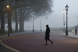 © Licensed to London News Pictures. 03/03/2021. London, UK. An early riser crosses a foggy Horse Guards Road in Westminster, central London.  Later Chancellor Rishi Sunak will deliver his budget to Parliament. Photo credit: Peter Macdiarmid/LNP