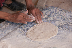 Middle East, Israel, Laqiya, Bedouin woman's hands kneading dough for flatbread to be cooked over fire.  MR