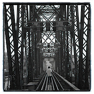 A man walks in the middle of long bien bridge's railway. Nice perspective with the metallic structure of that famous and old bridge.