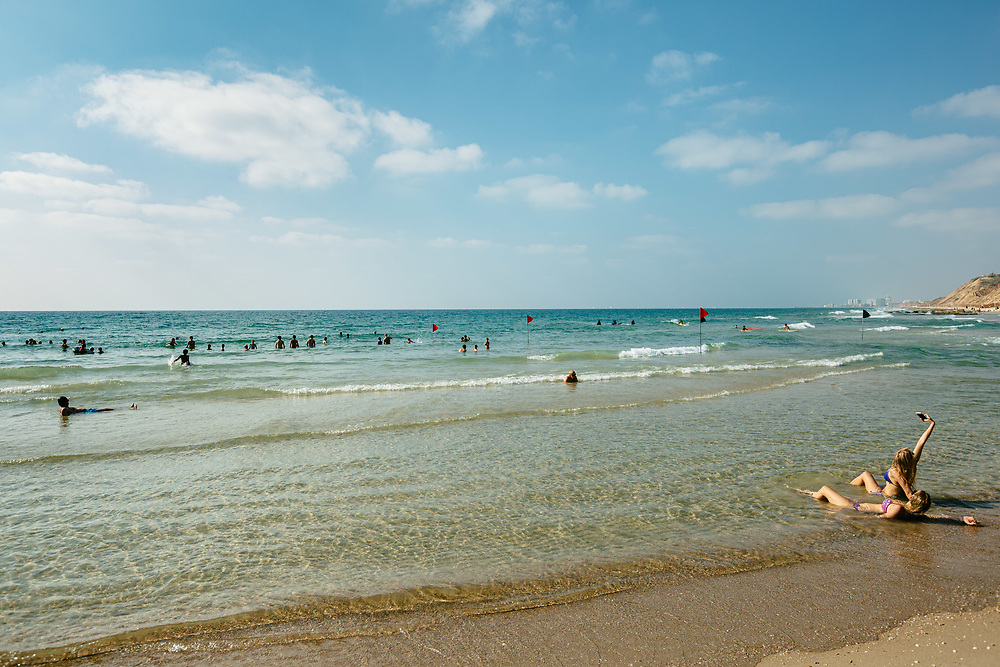 People enjoy a hot summer afternoon at Tel Baruch Beach in Tel Aviv, Israel
