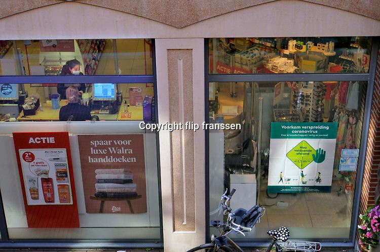 Nederland, Nijmegen, 25-3-2020 Een vrouw met mondkapje op rekent af bij drogisterij Etos. Ze heeft Nutrilon gekocht . Foto: Flip Franssen