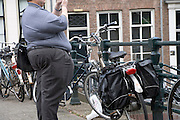 a very obese man standing near bicycles in Amsterdam, Sint Antonie sluis, Jodenbree straat, bridge, Holland