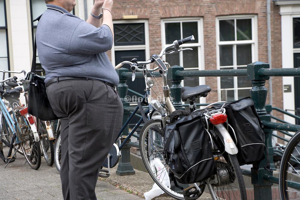 a very obese man standing near bicycles in Amsterdam, Sint Antonie sluis, Jodenbree straat, bridge, Holland