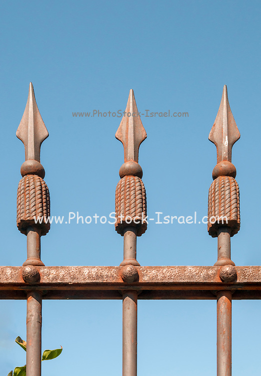 wrought iron spear like spikes on a fence on a blue sky background