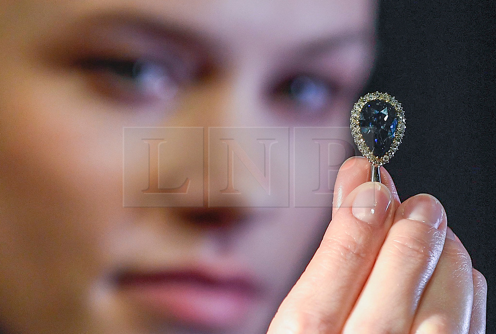 """© Licensed to London News Pictures. 06/04/2018. LONDON, UK. A model presents """"The Farnese Blue"""", a 6.16-carat, pear-shaped, fancy, dark grey-blue diamond, with an estimate of US$3.7-5.3m, at a photocall at Sotheby's, New Bond Street.  The diamond was presented to Elisabeth Farnese, Queen of Spain in 1715 and has been passed down through four of Europe's royal families.  The diamond will be sold at auction in Geneva on 15 May.  Photo credit: Stephen Chung/LNP"""