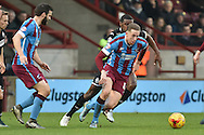 Kevin van Veen of Scunthorpe United takes ball from Donervon Daniels of Wigan Athletic  during the Sky Bet League 1 match between Scunthorpe United and Wigan Athletic at Glanford Park, Scunthorpe, England on 2 January 2016. Photo by Ian Lyall.