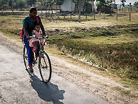 Woman and her child riding a bike on the road to Nepalgunj, Nepal.