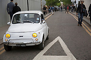 "Man in a tiny Fiat 500 car on Portobello Road in West London, UK. The Fiat 500 is a city car produced by the Italian manufacturer between 1957 and 1975. Launched as the Nuova (new) 500 in July 1957, it was a cheap and practical town car. Measuring only 2.97 metres (9 feet 9 inches) long, and originally powered by an appropriately sized 479 cc two-cylinder, air-cooled engine, the 500 redefined the term ""small car"" and is considered one of the first city cars."