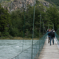 Hikers cross Pingo River near Grey Lake in Torres del Paine National Park, Chile.