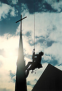 Construction worker erects steeple.