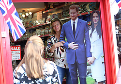 Tourist take pictures with a life size cutout of Prince Harry and fiancee Meghan Markle displayed in a gift shop, ahead the royal wedding on May 19.
