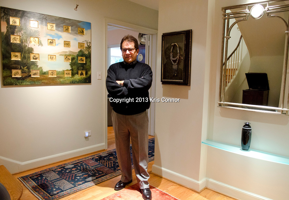 """Mario Castillo of The Aegis Group poses for a portrait in front of  his """"View From Fern tree Walk With Mating Species"""" painting at his home in northwest Washington D.C. on January 11, 2013. Photo by Kris Connor"""