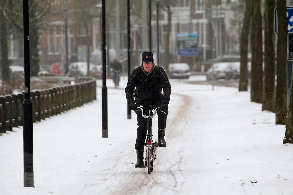 Een man op een vouwfiets rijdt op de Zijpendaalseweg in Arnhem door de sneeuw.<br /> <br /> A man on a folding bike is cycling at the Zijpendaalseweg in Arnhem in the snow.