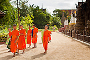 23 JUNE 2011 - CHIANG MAI, THAILAND: Novice monks walk out of Wat Pan Tao in Chiang Mai, Thailand. Wat Pan Tao is famous for its teak wood viharn that was once a royal residence. Most boys in Thailand enter the Buddhist clergy, called the Sangha, for at least a few months of their lives. Photo by Jack Kurtz