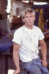 good looking blond man taking a break from working on a car