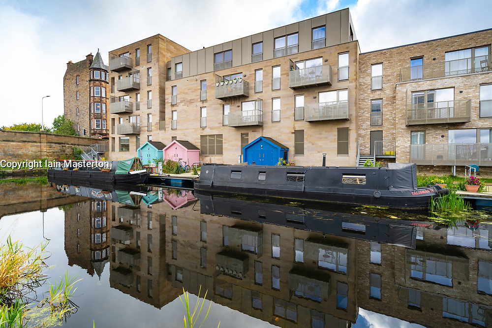 Modern apartment blocks and narrow boats moored along the Union Canal at Fountainbridge in Edinburgh, Scotland, UK