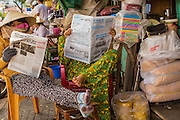 "12 APRIL 2012 - HO CHI MINH CITY, VIETNAM: Vendors read a newspaper in a neighborhood in Binh Tay Market. The market is warren of narrow halls and alleys and steep staircases and still relies on manual labor to move goods. Binh Tay market is the largest market in Ho Chi Minh City and is the central market of Cholon. Cholon is the Chinese-influenced section of Ho Chi Minh City (former Saigon). It is the largest ""Chinatown"" in Vietnam. Cholon consists of the western half of District 5 as well as several adjoining neighborhoods in District 6. The Vietnamese name Cholon literally means ""big"" (lon) ""market"" (cho). Incorporated in 1879 as a city 11 km from central Saigon. By the 1930s, it had expanded to the city limit of Saigon. On April 27, 1931, French colonial authorities merged the two cities to form Saigon-Cholon. In 1956, ""Cholon"" was dropped from the name and the city became known as Saigon. During the Vietnam War (called the American War by the Vietnamese), soldiers and deserters from the United States Army maintained a thriving black market in Cholon, trading in various American and especially U.S Army-issue items.             PHOTO BY JACK KURTZ"