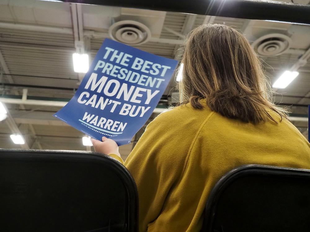 "Elizabeth Warren supporter holds sign ""The Best President Money Can't Buy: Warren"""