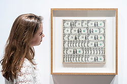"""© Licensed to London News Pictures. 08/06/2015. London, UK. A Sotheby's staff member looks at """"Dollar Bills"""" by Andy Warhol (est. £120k - £180k), at the preview of """"To the Bearer on Demand"""", a private collection of 21 works inspired by the US dollar, including Andy Warhol masterpieces, which will be auctioned on 1 and 2 July.  The collection is estimated to realise £50 million. Photo credit : Stephen Chung/LNP"""