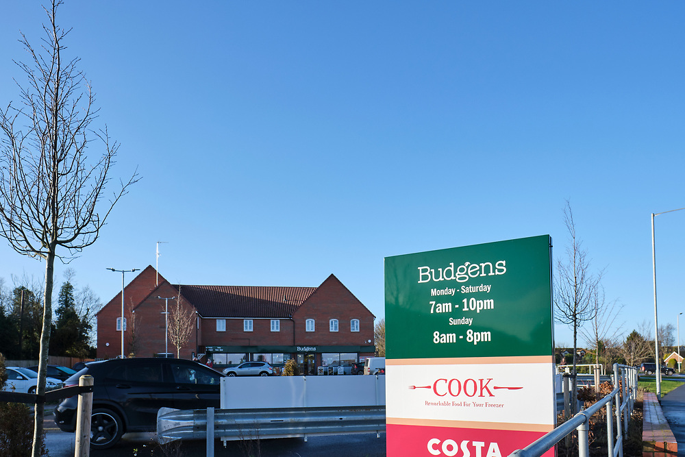 Road side sign for the Budgens store, showing opening times. The store can be seen in the backgrounders with a car entering the car part on the left.<br /> <br /> Photo by Jonathan J Fussell, COPYRIGHT 2020