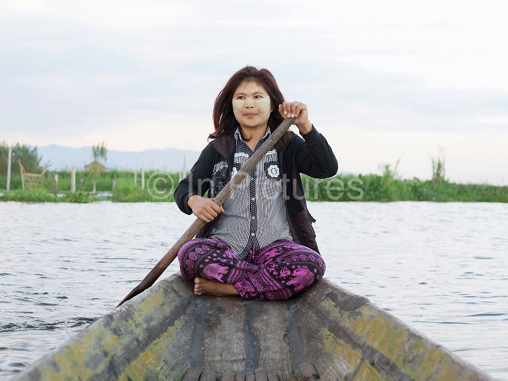 An Intha woman rowing a wooden boat at Nam Pan village on Inle Lake, Shan State, Myanmar on 7th November 2016