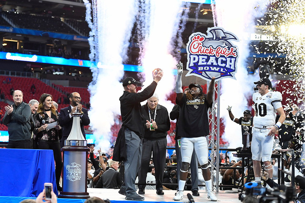 UCF Knights head coach Scott Frost, linebacker Shaquem Griffin (C), and quarterback McKenzie Milton (10) celebrate after the second half of the Chick-fil-A Peach Bowl NCAA college football game at the Mercedes-Benz Stadium in Atlanta, January 1, 2018. UCF won 34-27 to go undefeated for the season. (David Tulis via Abell Images for Chick-fil-A Peach Bowl)