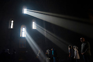 With people gathered for a service, beams of morning sunlight stream into the church at Tatev Monastery in Armenia.