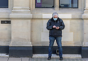 22nd February, Cheltenham, England. A man stands outside HSBC, wearing a mask during the third national lockdown in England.