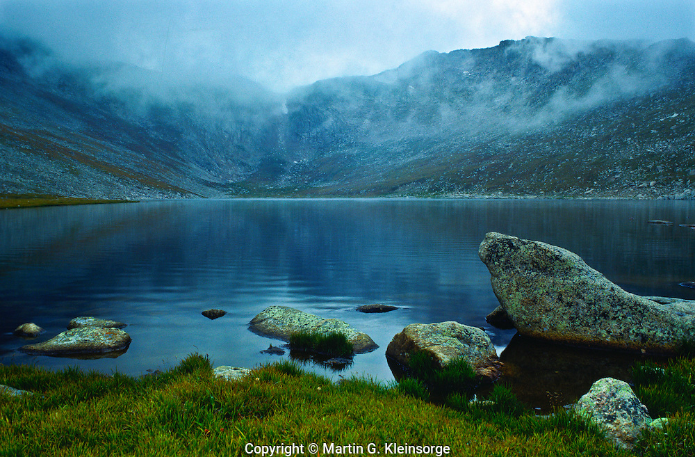 Stratus clouds creating fog and drizzle over Summit Lake on Mount Evans, Colorado.
