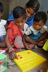 RENUBALA KEI is the teacher in a preschool in ICHHAPUR village.  She is helping play a game with a group of children with letters which need to fit in their corresponding letter-shaped place. RAJESWARI DASH 4 years old in red dress and an unnamed girl on the right. They are sitting on the balcony area of their small class room. This is one of many supported kindergartens that PREM works with in villages in Orissa and Andhra Pradesh states of India