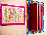 "09 AUGUST 2014 - BANGKOK, THAILAND:       A Chinese prayer on the wall at the Ruby Goddess Shrine in the Dusit section of Bangkok. The seventh month of the Chinese Lunar calendar is called ""Ghost Month"" during which ghosts and spirits, including those of the deceased ancestors, come out from the lower realm. It is common for Chinese people to make merit during the month by burning ""hell money"" and presenting food to the ghosts. At Chinese temples in Thailand, it is also customary to give food to the poorer people in the community.   PHOTO BY JACK KURTZ"
