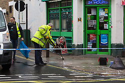 Soutwark Council workers clean the pavement where a man in his 30s was stabbed outside an off licence in the early hours of Sunday February 10th on Lordship Lane, East Dulwich in London. London, February 10 2019.