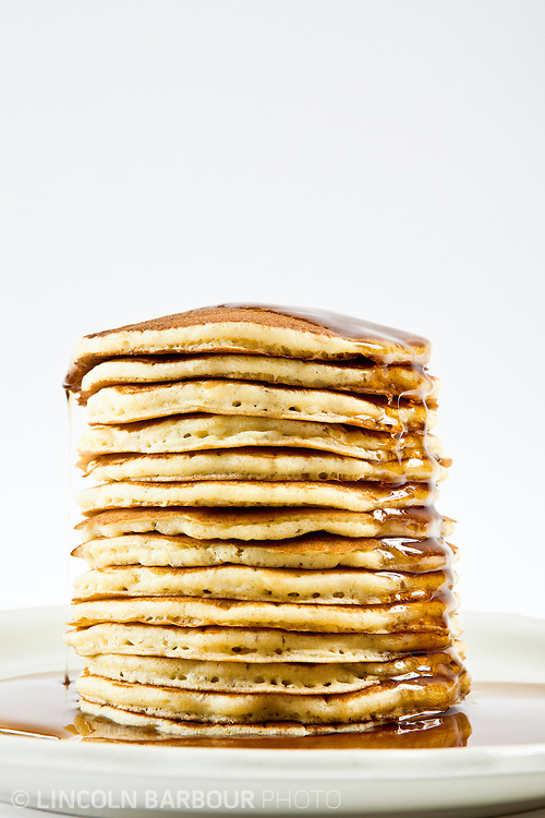 A large stack of silver dollar pancakes covered in syrup