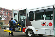 """Nofomuli Finaulahi helps Bruce Oka onto the San Francisco Paratransit Bus the """"Grayce Reagan"""" at Fort Point in front of the Golden Gate Bridge"""