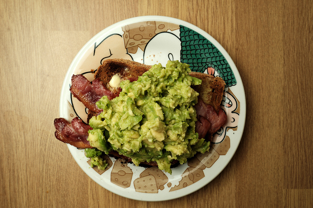 Tasty thick bacon under a pile of mashed up avocado on a home made wholemeal bread toasted not to perfection.<br /> <br /> On a Wallace & Gromit plate.<br /> <br /> A project to capture the everyday food I eat at home.<br /> Inspired by Real Food & Dimly Lit Meals, taken during the tail end of an extended isolation during the pandemic.<br /> <br /> <br /> Photo by Jonathan J Fussell, COPYRIGHT 2021