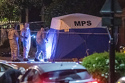 © Licensed to London News Pictures. 19/05/2020. London, UK. Forensic investigators enter a police tent on Wiltshire Gardens. Police were called at 20:22BST to reports of shots fired in Wiltshire Gardens in Haringey. Metropolitan Police Service attended along with London Ambulance Service and found a man, believed to be aged in his 20s, suffering gunshot injuries. The man was pronounced dead at the scene. Photo credit: Peter Manning/LNP