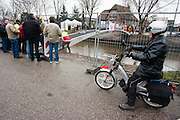 Een man op een brommer kijkt hoe een speciale fietsbrug over de Leidsche Rijn in Utrecht wordt geplaatst.<br /> <br /> A man on a moped is watching how a special bridge for cyclists is being placed over the Leidsche Rijn near Utrecht