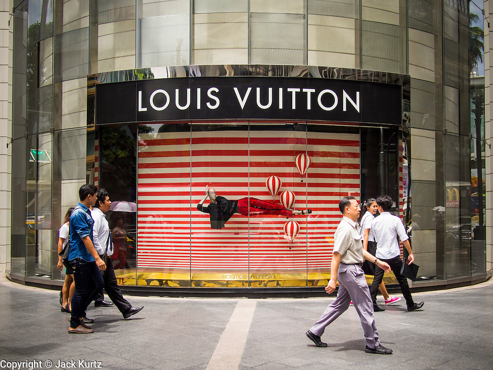 """23 AUGUST 2013 - BANGKOK, THAILAND:    Pedestrians walk past a Louis Vuitton store in Bangkok. Thailand entered a """"technical"""" recession this month after the economy shrank by 0.3% in the second quarter of the year. The 0.3% contraction in gross domestic product between April and June followed a previous fall of 1.7% during the first quarter of 2013. The contraction is being blamed on a drop in demand for exports, a drop in domestic demand and a loss of consumer confidence. At the same time, the value of the Thai Baht against the US Dollar has dropped significantly, from a high of about 28Baht to $1 in April to 32THB to 1USD in August.    PHOTO BY JACK KURTZ"""