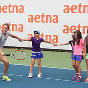 August 16, 2014, New Haven, CT:<br /> Andrea Petkovic leads a chain of kids as she hits a backhand during a tennis clinic in the AETNA FitZone as part of Kids Day on day three of the 2014 Connecticut Open at the Yale University Tennis Center in New Haven, Connecticut Sunday, August 17, 2014.<br /> (Photo by Billie Weiss/Connecticut Open)