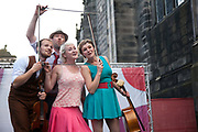 A violin playing quartet are advertising their play in the Royal Mile during the Edinburgh Festival.