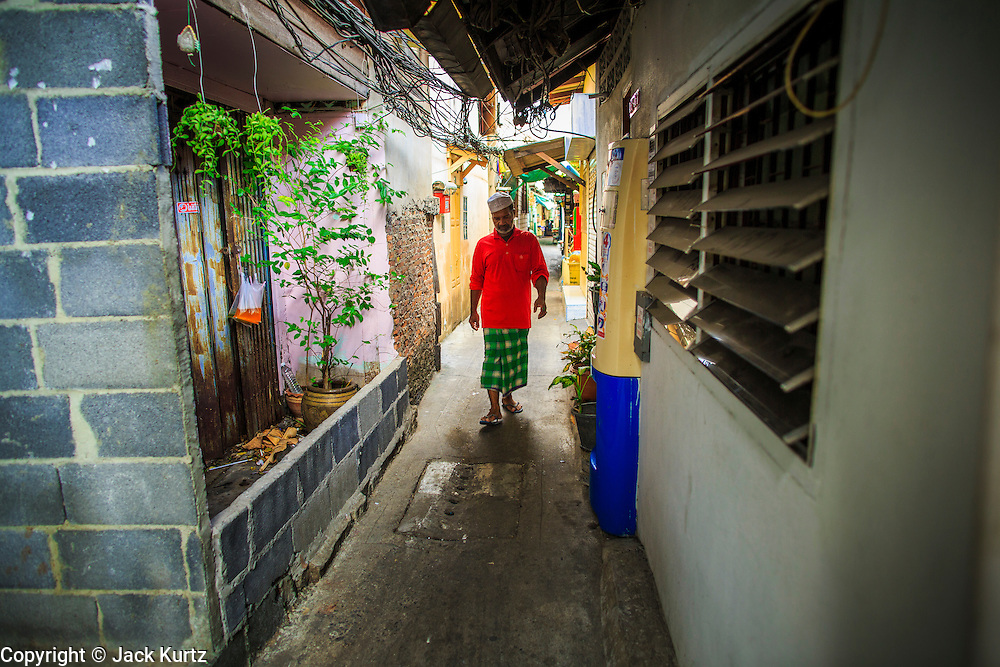 """10 JANUARY 2013 - BANGKOK, THAILAND:    A Muslim man walks through the Baan Krua neighborhood in Bangkok. The Ban Krua neighborhood of Bangkok is the oldest Muslim community in Bangkok. Ban Krua was originally settled by Cham Muslims from Cambodia and Vietnam who fought on the side of the Thai King Rama I. They were given a royal grant of land east of what was then the Thai capitol at the end of the 18th century in return for their military service. The Cham Muslims were originally weavers and what is known as """"Thai Silk"""" was developed by the people in Ban Krua. Several families in the neighborhood still weave in their homes.   PHOTO BY JACK KURTZ"""
