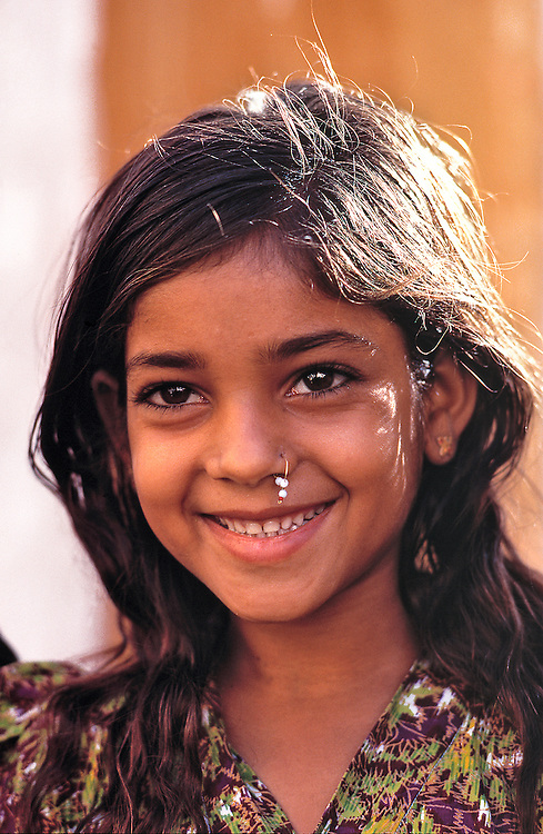 A young Rajasthani girl smiles a friendly greeting in Jaiselmeer, Rajasthan, India.