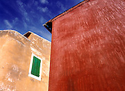 The primary colors displayed by painted walls against a blue sky are accented by looking upward from a low perspective, in Rousillion, Provence, France.
