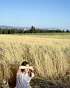 young woman sitting in a crop of oats with arm in front of eyes blocking the sun.