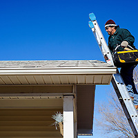 011014       Cable Hoover<br /> <br /> Construction contractor Chris Chavez carries his bag of tools onto the roof of a Habitat for Humanity home in Gallup to begin the final installation of solar panels Friday.