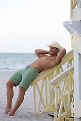 sexy man in a bathing suit leaning on a lifeguard stand in Florida