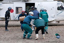 © under license to London News Pictures. 19/03/2011. On the mountains overlooking Onagawa a Japanese Military Self Defence helicopter distributes food and supplies to stranded villagers today (19/03/2011). Photo credit should read London News Pictures. Photo credit should read: London News Pictures