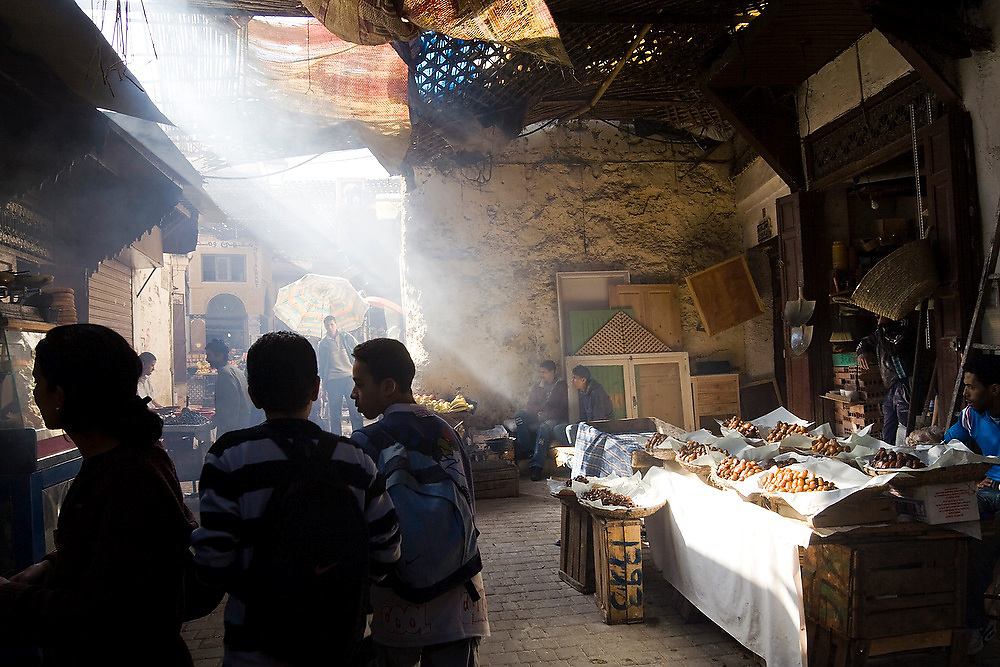 A shaft of light illuminates piles of large dried dates on sale at a street stall in a busy dark alley in Fes El-Bali, Morocco.