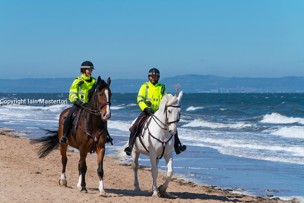 Portobello, Scotland, UK. 19 April 2020. Mounted police horses Logie and Edinburgh - in white , patrol the promenade and beach at Portobello on sunny Sunday afternoon. Iain Masterton/Alamy Live News